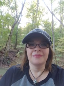 It's me, in the woods, wearing a cap and the mildly creepy eye  necklace I break out every year at Halloween.